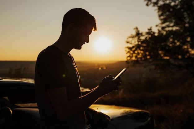 Schattenbild des mannes, der mit dem auto reist und mit einem mobiltelefon auf dem hügel während des herrlichen sonnenuntergangs steht.