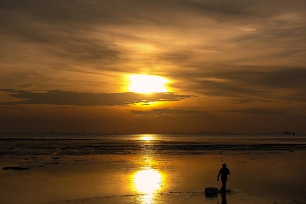 Schattenbild des mannes gehend auf den strand bei sonnenaufgang