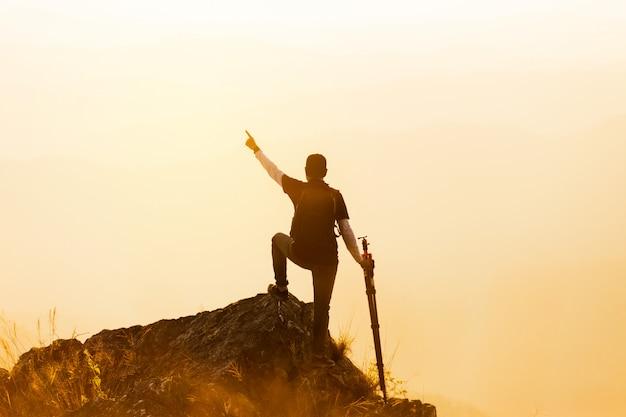 Schattenbild des mannes halten hände auf der spitze des berges, erfolgskonzept hoch