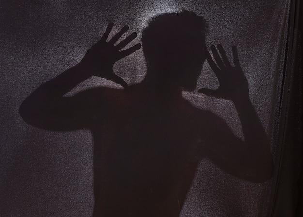 Schattenbild des mannes hinter dunklem stoff
