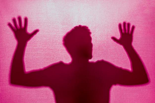 Schattenbild des mannes hinter stoff eingeschlossen