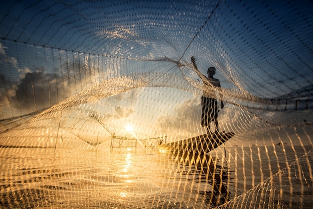 Schattenbild des mannes mit fischnetzen am morgen bei pakpra, phatthalung, thailand