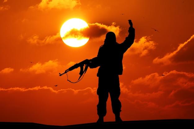 Schattenbild des militärsoldaten mit der waffe bei sonnenuntergang