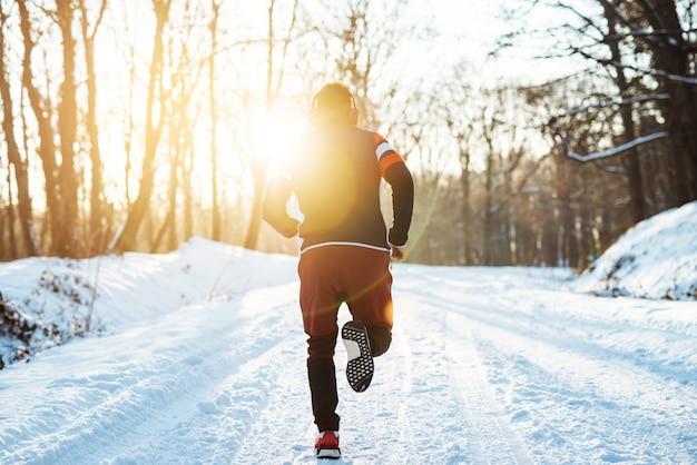 Schattenbild des muskulösen jungen mannes, der bei sonnenaufgang im winter hinkt