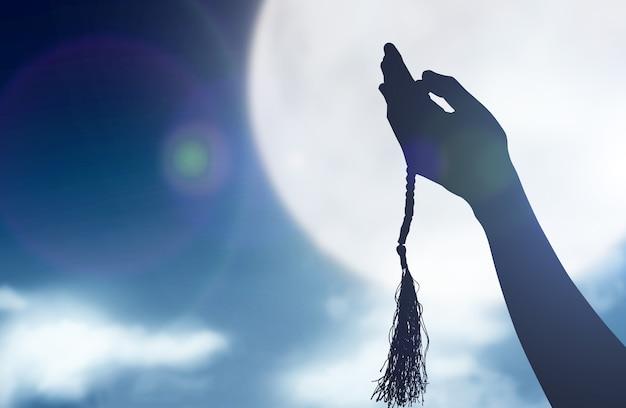 Schattenbild des muslimischen mannes, der mit gebetsperlen auf seinen händen mit einem nachtszenenhintergrund betet