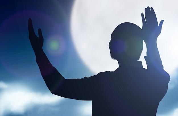 Schattenbild des muslimischen mannes stehend, während erhobene hände und betend