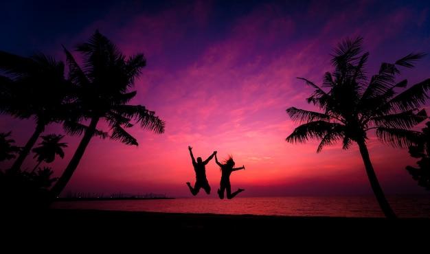 Schattenbild des paares am tropischen strand während des sonnenuntergangs auf hintergrund der palmen