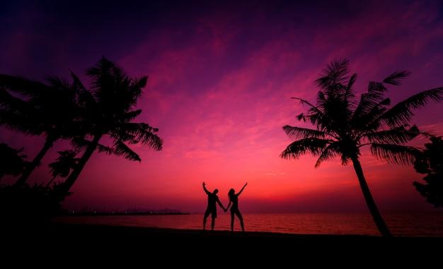 Schattenbild des paares am tropischen strand während des sonnenuntergangs auf hintergrund