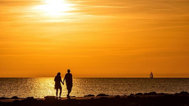 Schattenbild des paares, das auf dem pier während der goldenen stunde des sonnenuntergangs geht