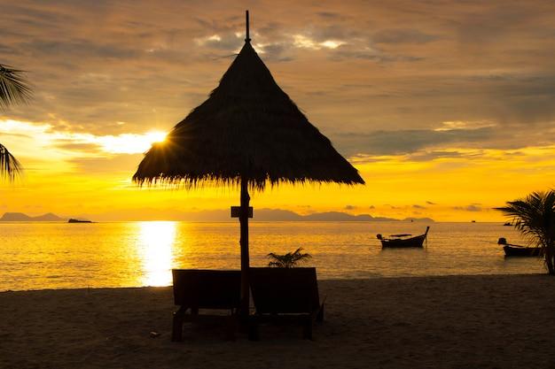 Schattenbild des pavillons auf der schönen farblandschaftshimmeldämmerung des strandes in der natur