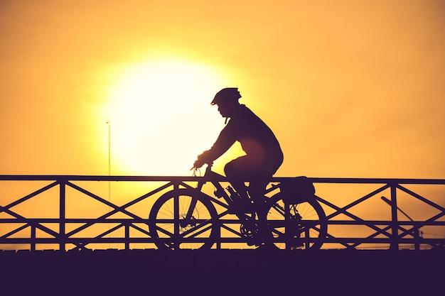 Schattenbild des radfahrers auf brücken- und sonnenuntergangweinlesefarbe