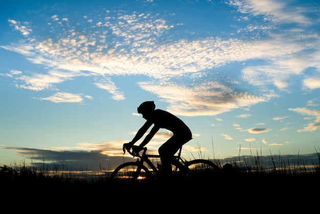 Schattenbild des radfahrers ein rennrad auf offene straße am abend während des sonnenuntergangs reiten