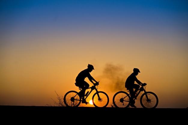 Schattenbild des radfahrers mit mountainbike auf schöner sonnenuntergangzeit