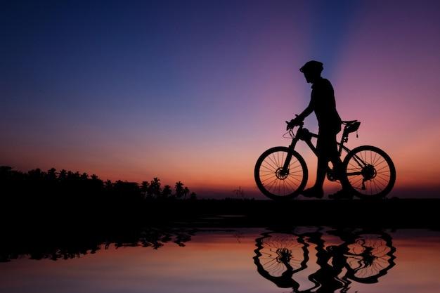 Schattenbild des radfahrers mit mountainbike auf schöner sonnenuntergangzeit.