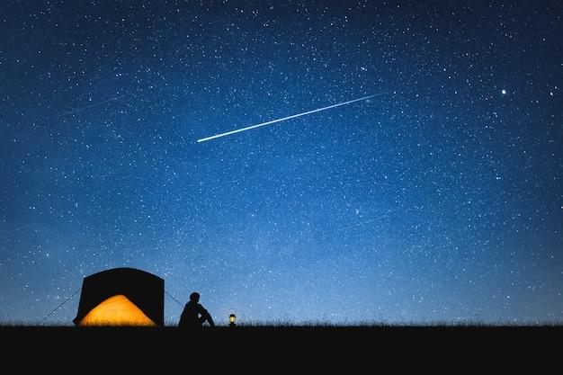 Schattenbild des reisenden kampierend auf dem berg und dem nächtlichen himmel mit sternen. raum hintergrund.