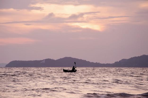 Schattenbild des ruderbootboots der leute auf dem meer bei sonnenuntergang