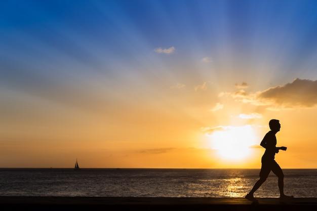 Schattenbild des rüttelnden mannes am strand mit sonnenunterganghintergrund