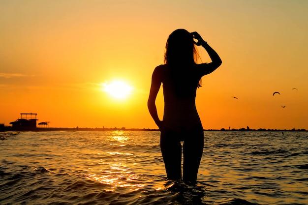 Schattenbild des schönen hohen modells, das im wasser des ozeans während eines sonnenaufgangs steht