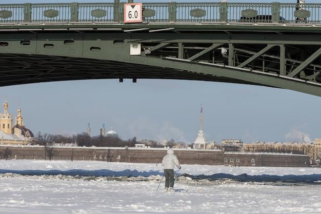 Schattenbild des skifahrers, der auf eis des gefrorenen sees reitet