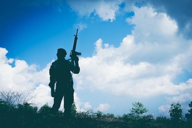 Schattenbild des soldaten mit gewehr gegen die sonne