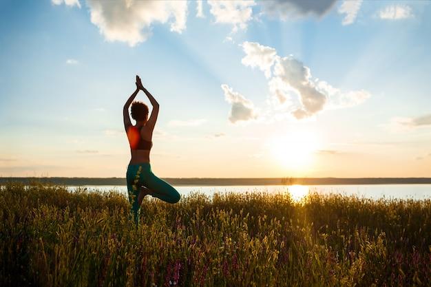 Schattenbild des sportlichen mädchens, das yoga im feld bei sonnenaufgang praktiziert.