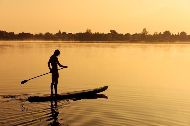 Schattenbild des starken sportlichen mannes, der langes paddel für das schwimmen auf sup brett während der morgenzeit auf see verwendet.