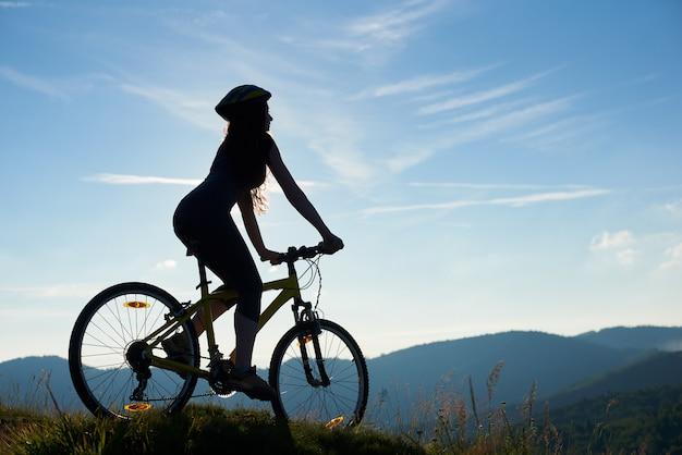 Schattenbild des starken weiblichen radfahrers, der auf mountainbike am sonnigen morgen fährt