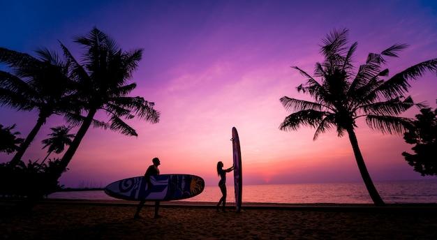 Schattenbild des surferpaares, das lange surfbretter bei sonnenuntergang hält