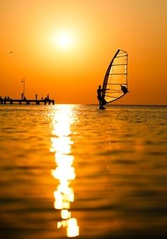 Schattenbild des surfers am sonnenuntergang, der vorbei überschreitet