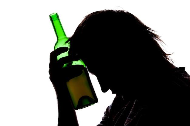 Schattenbild des traurigen mannes, der alkohol trinkt