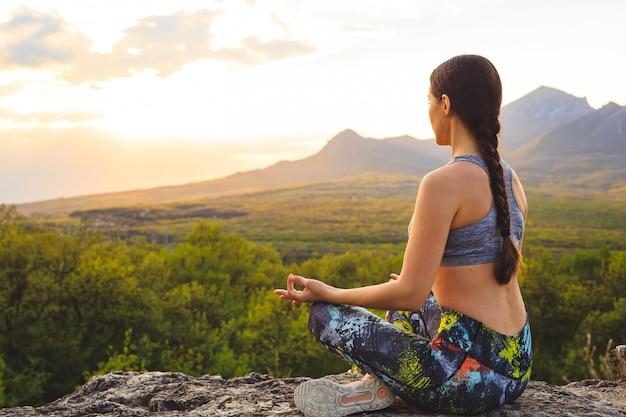 Schattenbild des übenden yoga der jungen frau bei sonnenuntergang