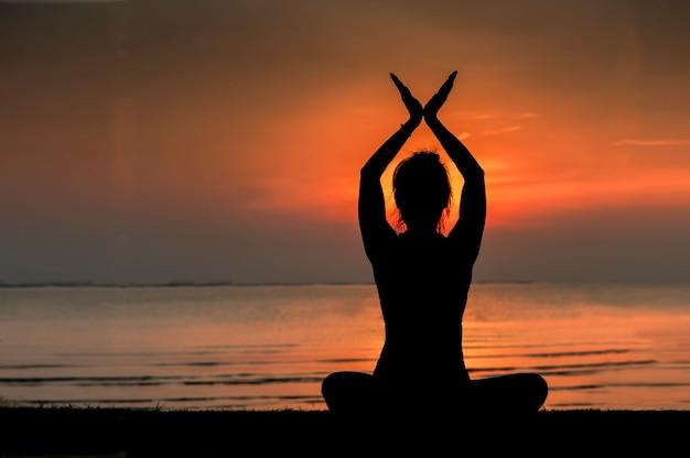 Schattenbild des übenden yoga des jungen schönen mädchens, dort ist ein orange sonnenuntergang im backgr