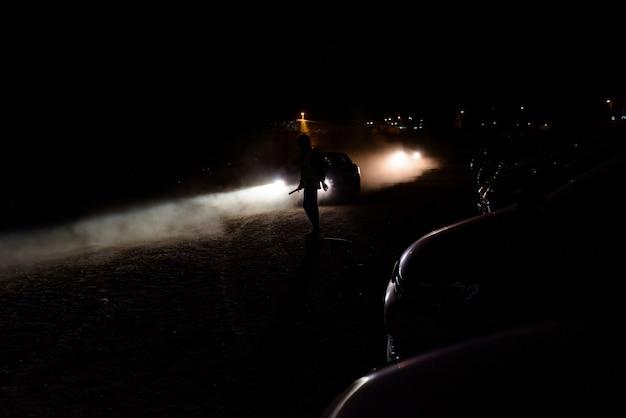 Schattenbild des unerkennbaren mannes belichtet durch die scheinwerfer eines autos in einer dunklen nacht.