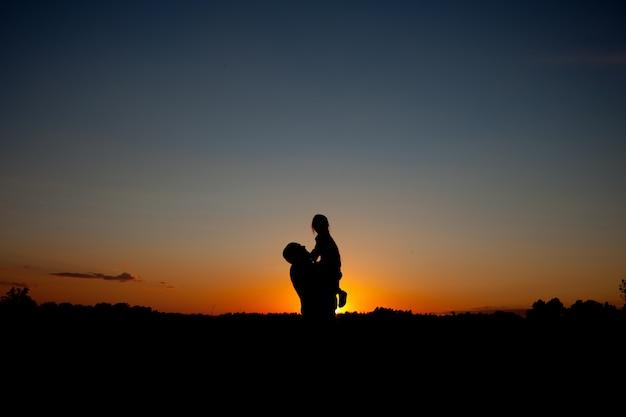 Schattenbild des vaters und des kindes auf dem im freien auf schönem sommersonnenuntergang - familie