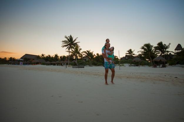 Schattenbild des vaters und seiner zwei kleinen töchter im sonnenuntergang auf dem strand in tulum, mexiko