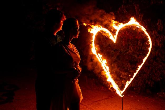 Schattenbild des verliebten paares nahe brennenden feuerbuchstaben liebe und herz