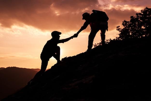 Schattenbild des wanderers, der einander hilft, einen berg bei sonnenuntergang zu wandern.