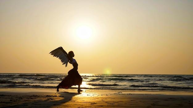 Schattenbild des weiblichen engels am strand bei sonnenuntergang