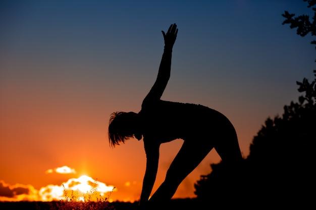 Schattenbild des weiblichen erwachsenen, der yoga im freien in