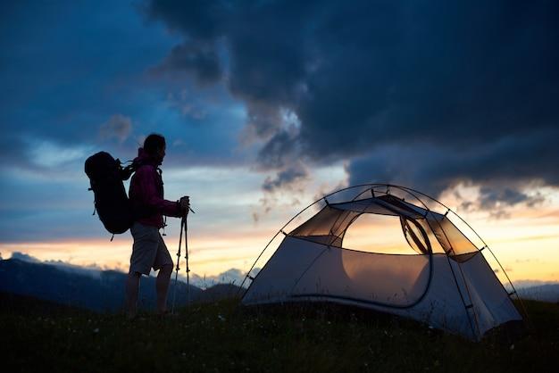 Schattenbild des weiblichen touristen nahe dem zelt mit rucksack auf ihren schultern und gehstöcken in den händen, die sonnenuntergangansicht über berghügeln genießen. konzept für reisen und aktive lebensweise.