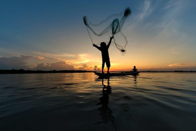 Schattenbild des werfenden netzes des fischers auf bootsfischen in see