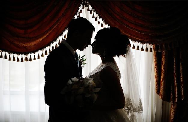 Schattenbild einer braut und des bräutigams auf dem hintergrund des fensters. braut und bräutigam küssen auf dem hintergrund des fensters.