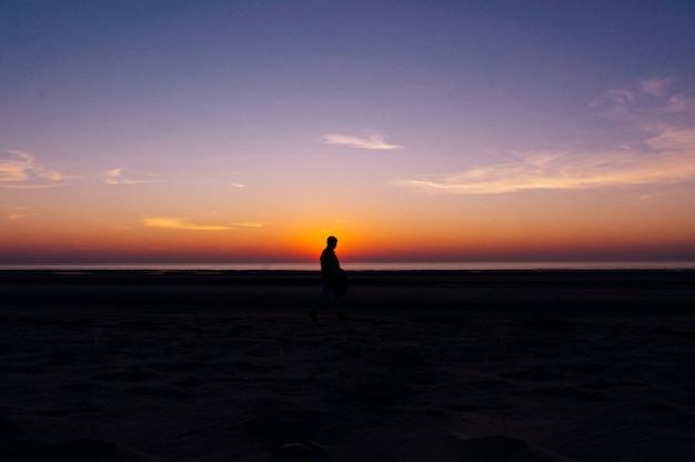 Schattenbild einer einsamen person, die auf dem strand mit der schönen ansicht des sonnenuntergangs im hintergrund geht