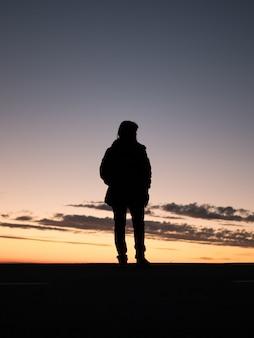 Schattenbild einer einsamen person, die den schönen blick auf den sonnenuntergang genießt