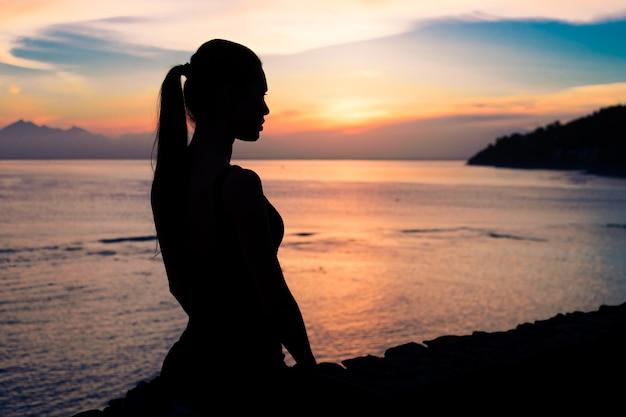 Schattenbild einer frau, die an einem strand sitzt
