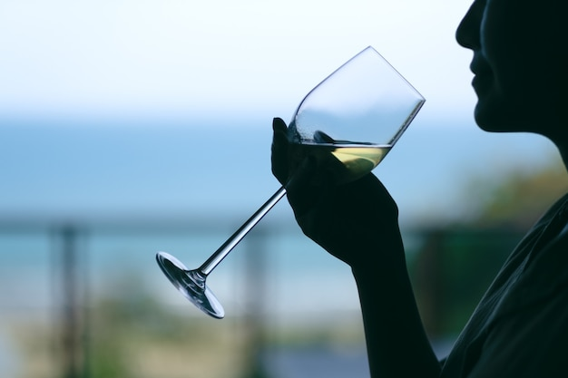 Schattenbild einer frau, die ein weinglas hält, um mit unscharfem meereshintergrund zu trinken