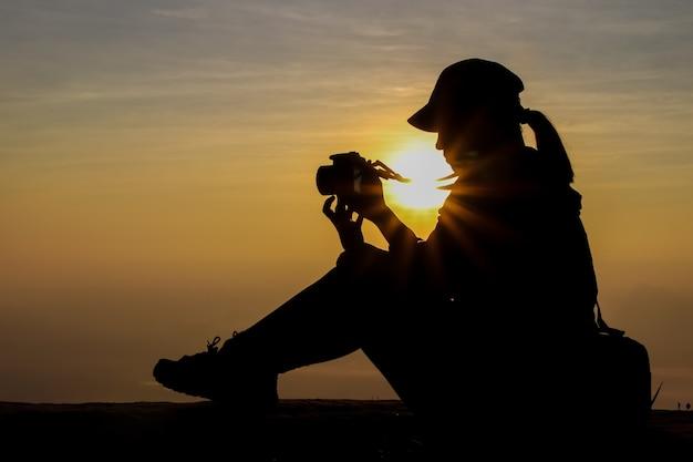 Schattenbild einer frau, die eine kamera hält, die bilder draußen während sonnenaufgang oder sonnenuntergang macht