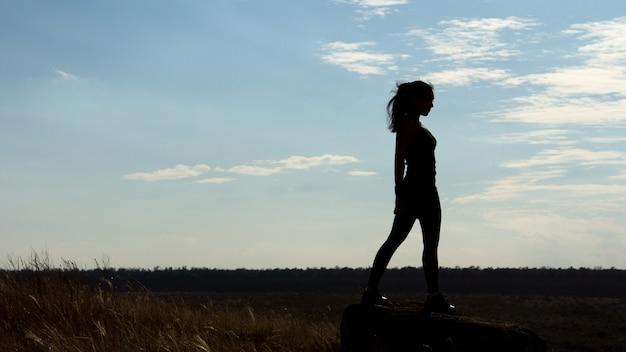Schattenbild einer gesunden gesunden sexy frau, die am horizont gegen einen späten nachmittagshimmel steht