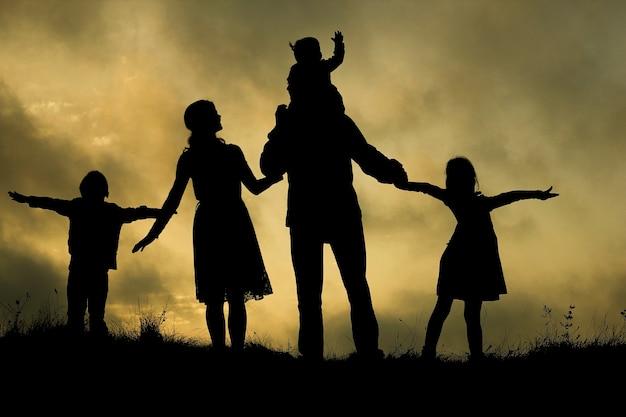 Schattenbild einer glücklichen familie mit kindern auf natur