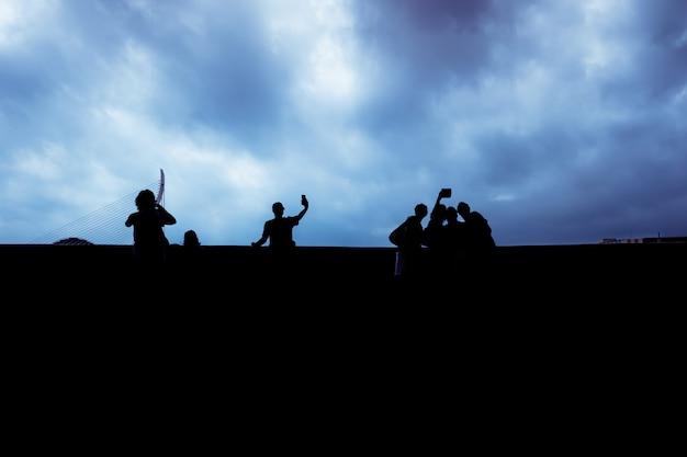 Schattenbild einer gruppe nicht erkennbarer leute, die ihre smartphones, sozial lokalisiert verwenden.
